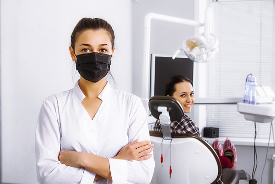 dentist in black mask with patient in office